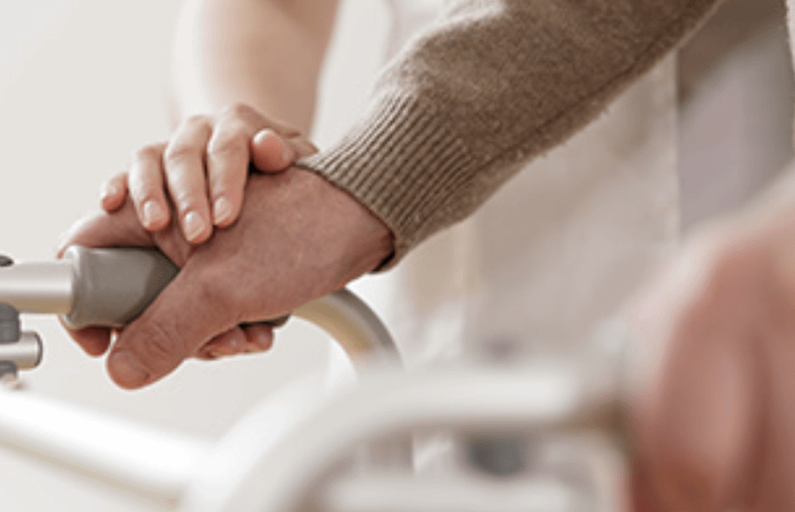 Elderly person and younger person holding hands